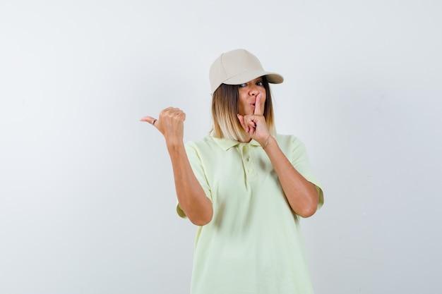 Tシャツ、キャップ、自信を持って、正面図で親指で左側を指して、沈黙のジェスチャーを示す若い女性。