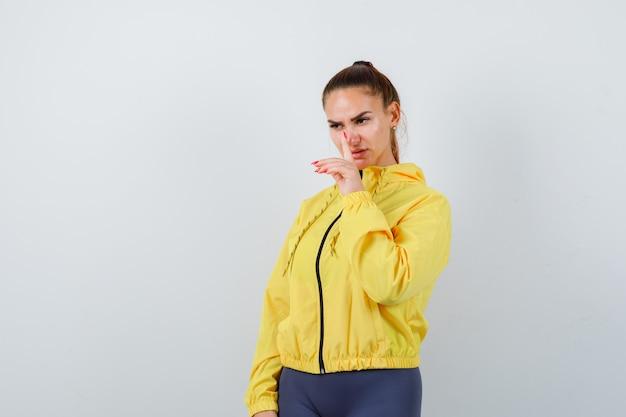 Giovane signora che mostra gesto di silenzio in giacca gialla e sembra seria. vista frontale.