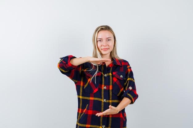 Giovane donna che mostra il segno di dimensioni in camicia a quadri e sembra fiduciosa, vista frontale.