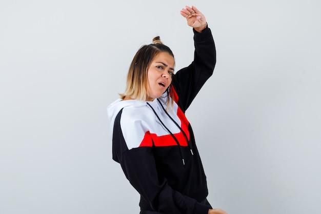 Giovane donna che mostra il segno della taglia in un maglione con cappuccio e sembra ansiosa