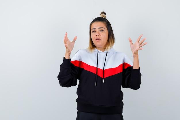 Giovane donna che mostra il segno della taglia in un maglione con cappuccio e sembra attenta