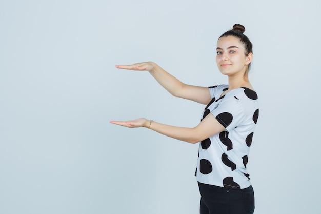 Tシャツ、ジーンズ、自信を持って、正面図でサイズサインを示す若い女性。