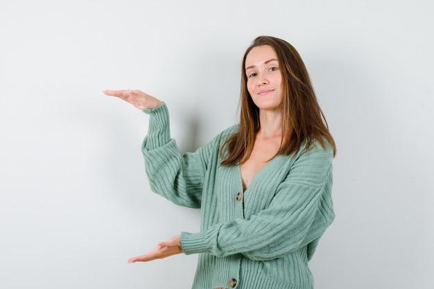 ウールのカーディガンでサイズサインを示し、自信を持って見える若い女性。正面図。