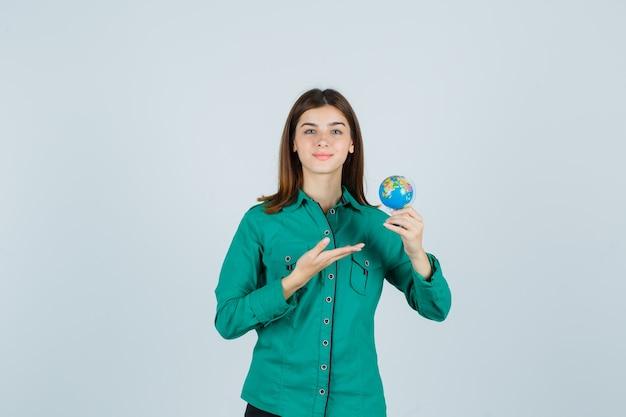 Giovane donna che mostra il piccolo globo terrestre in camicia e sembra soddisfatta, vista frontale.