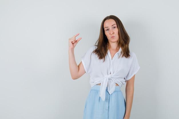 ブラウスとスカートで小さなサイズのサインを示し、自信を持って見える若い女性