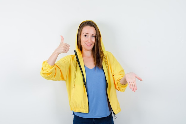 Tシャツ、ジャケット、自信を持って親指を立てて下に何かを示している若い女性