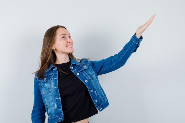 Giovane donna che mostra qualcosa sopra in camicetta, giacca e sembra felice. vista frontale.