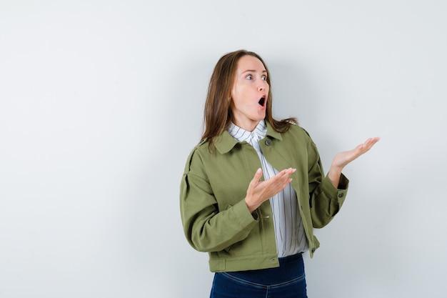 Giovane donna che mostra qualcosa sopra in camicetta, giacca e sembra sorpresa.