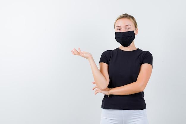 Tシャツ、ズボン、医療マスクで何かを示し、自信を持って見える若い女性