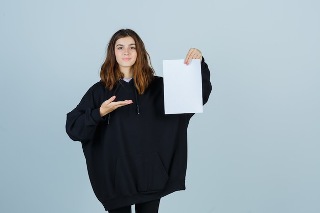 特大のパーカー、パンツで紙を保持し、自信を持って、正面図を見て何かを見せている若い女性。