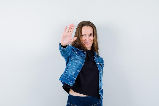 Giovane donna che mostra il gesto di arresto in camicetta, giacca e sembra sicura. vista frontale.