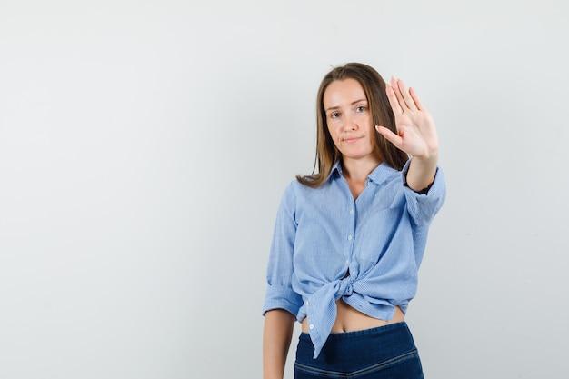 Giovane signora che mostra il gesto di arresto in camicia blu, pantaloni e guardando sicuro