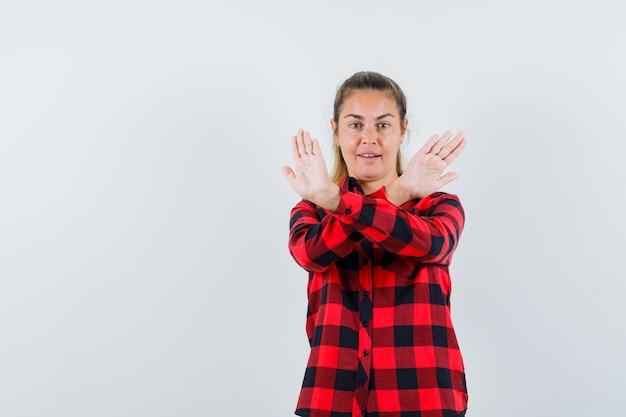 Giovane signora che mostra il gesto di arresto in camicia controllata e sembra sicura