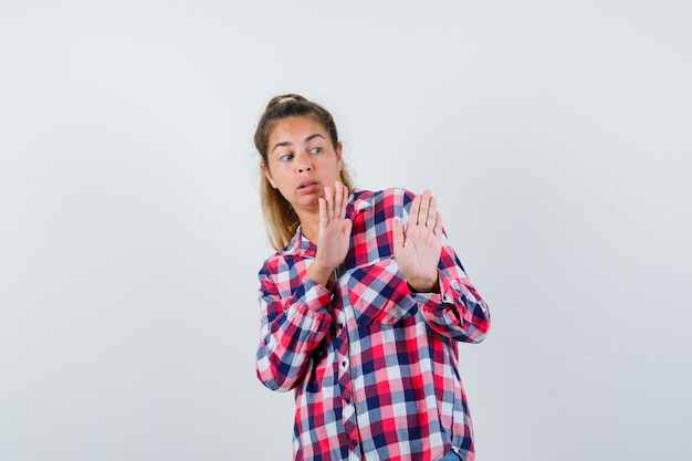 Young lady showing stop gesture in checked shirt and looking scared , front view.