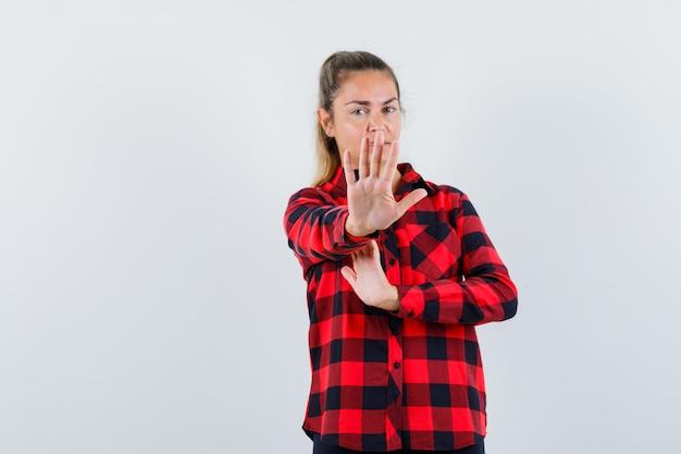 Giovane signora che mostra il gesto di arresto in camicia controllata e che sembra spaventata