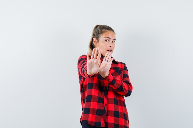 Young lady showing stop gesture in checked shirt and looking scared