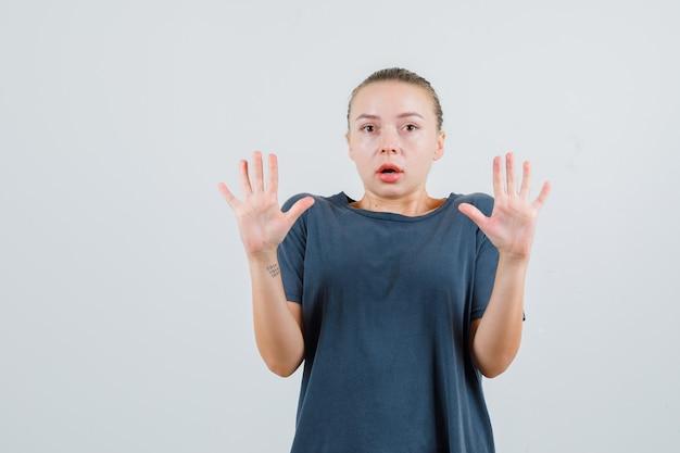 Giovane signora che mostra il gesto di arresto in maglietta grigia e che sembra spaventata