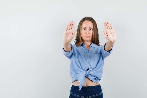 Молодая дама показывает жест стоп в синей рубашке, штанах и выглядит уверенно
