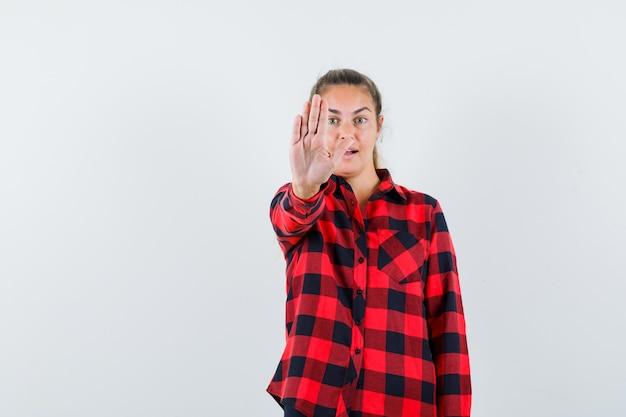カジュアルなシャツで停止ジェスチャーを示し、自信を持って見える若い女性。正面図。