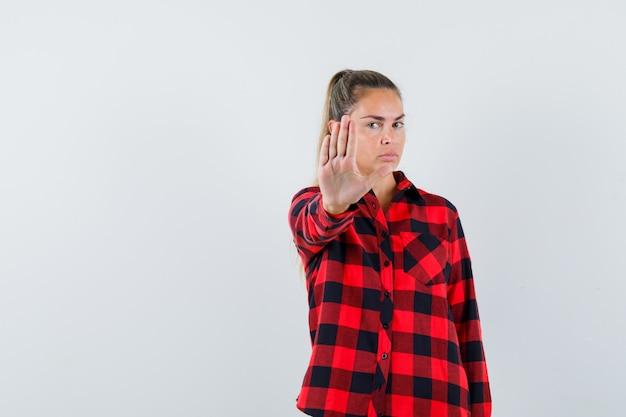カジュアルなシャツで停止ジェスチャーを示し、真剣に見える若い女性。正面図。