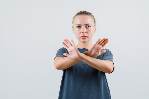 灰色のtシャツで停止ジェスチャーを示し、厳格に見える若い女性