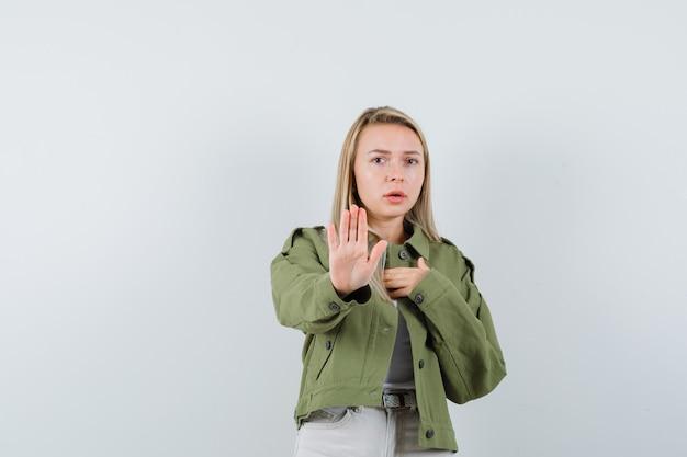 재킷, 바지에 중지 제스처를 보여주는 젊은 아가씨 불안, 전면보기를 찾고.