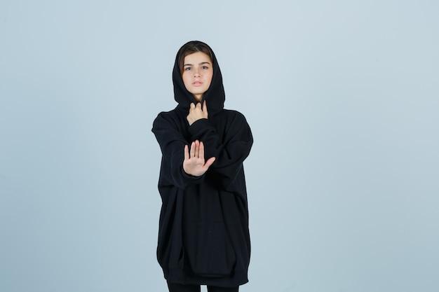 特大のパーカー、パンツで停止ジェスチャーを示し、真剣に見える若い女性。正面図。 無料写真