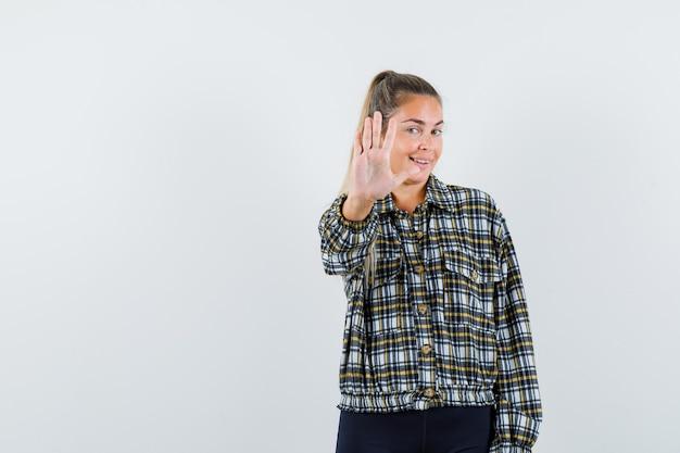 シャツ、ショートパンツ、自信を持って、正面図で停止ジェスチャーを示す若い女性。