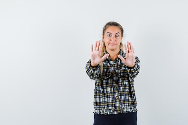 シャツ、ショートパンツで停止ジェスチャーを示し、怖がって見える若い女性。正面図。