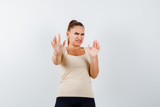 一重項で停止ジェスチャーを示し、うんざりしているように見える若い女性。正面図。