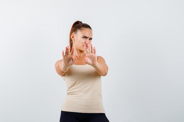 タンクトップで停止ジェスチャーを示し、うんざりしている若い女性。正面図。