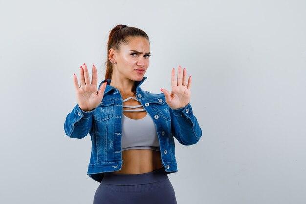 トップ、デニムジャケットで停止ジェスチャーを示し、真剣に見える若い女性。正面図。
