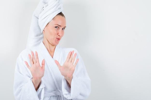 흰색 목욕 가운, 수건 및 현명한, 전면보기에 중지 제스처를 보여주는 젊은 아가씨.