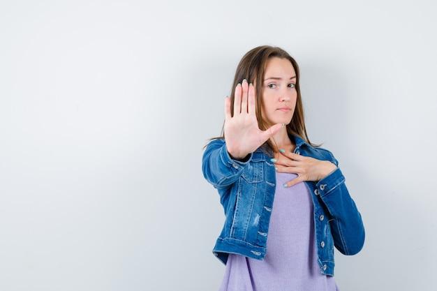 Giovane donna che mostra il gesto di arresto, tenendo la mano sul petto in maglietta, giacca e guardando seria, vista frontale.