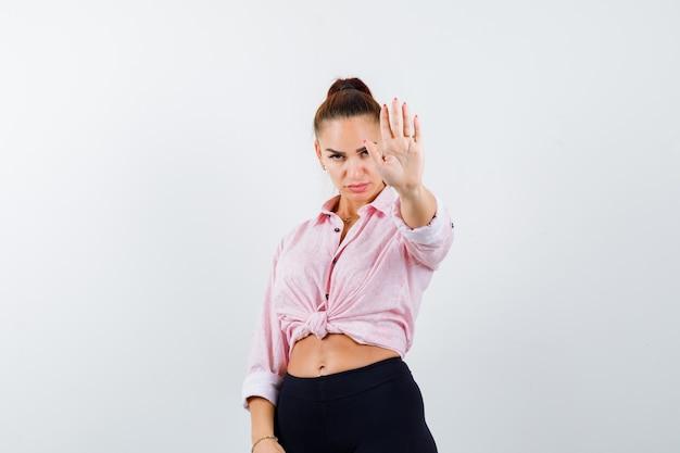 Giovane signora che mostra il gesto di arresto in camicia, pantaloni e guardando fiducioso, vista frontale.