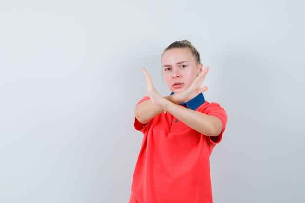 Giovane signora che mostra il gesto di arresto in maglietta e che sembra serio