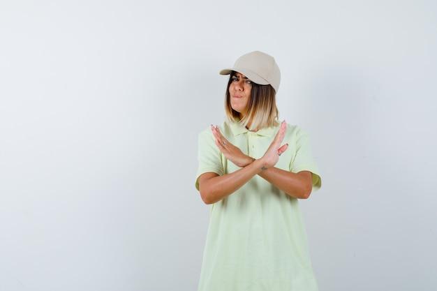 T- 셔츠, 모자에 입술을 삐 죽 고 심각한, 전면보기 동안 중지 제스처를 보여주는 젊은 아가씨.