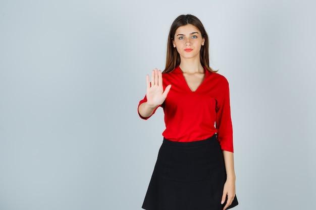 Молодая дама показывает знак остановки в красной блузке, черной юбке и выглядит счастливой