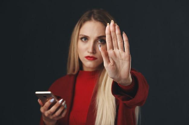 Девушка показывает знак остановки с телефоном в руке