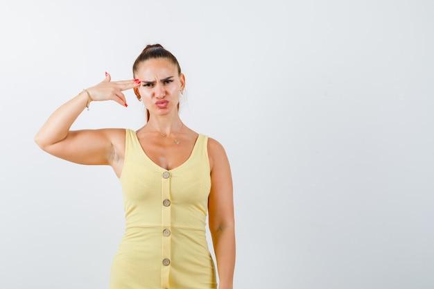 Giovane donna che mostra il gesto di suicidio in abito giallo e guardando cupo, vista frontale.