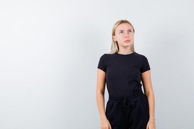 Giovane signora che mostra posa di pensiero in maglietta, pantaloni e sguardo cupo. vista frontale.