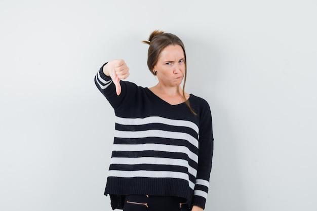 Giovane signora che mostra il pollice verso il basso in camicia casual e guardando malcontento