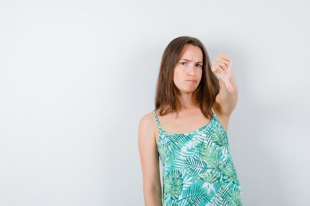 Giovane donna che mostra il pollice verso il basso, fa una smorfia e sembra dispiaciuta, vista frontale.