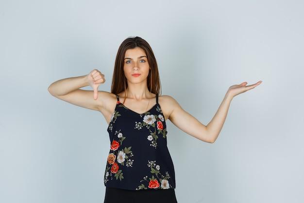 Giovane donna che mostra il pollice verso il basso, allargando il palmo in camicetta, gonna e guardando scontento, vista frontale.