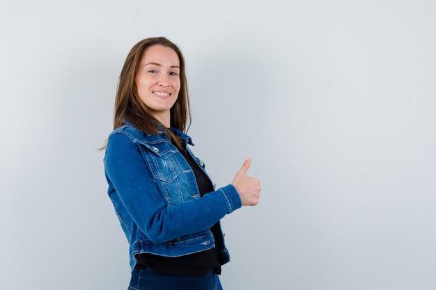Giovane donna che mostra pollice in camicetta, giacca e sembra felice. vista frontale.