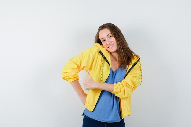 Tシャツ、ジャケットに肩をすくめてエレガントに見えることで親指を見せて若い女性