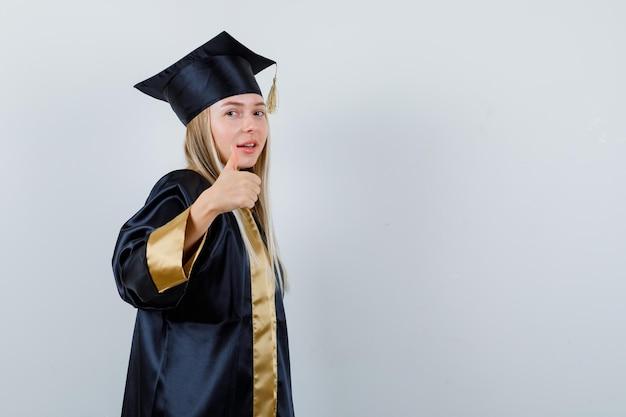 アカデミックドレスで親指を表示し、自信を持って見える若い女性