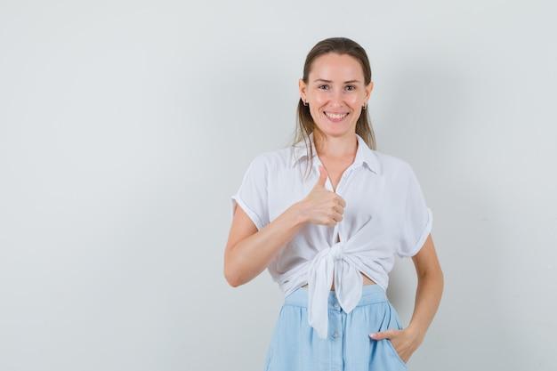 ブラウスとスカートで親指を表示し、幸せそうに見える若い女性
