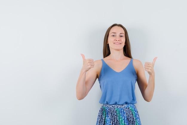 ブラウス、スカート、嬉しそうに見える、正面図で親指を示す若い女性。テキスト用のスペース