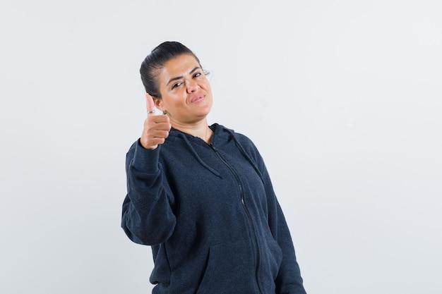 재킷에 엄지 손가락을 표시 하 고 낙관적 찾고 젊은 아가씨. 전면보기.